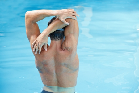 13635560 - young man doing back exercises in blue water in swimming pool