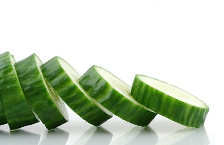 2189446 - cucumber slices reflecting in a white background.