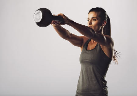 24327653 - image of young attractive female doing kettle bell exercise on grey background. fitness woman working out. crossfit exercise.