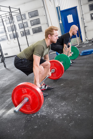 29352977 - two men taking deadlifts at crossfit center. weight workout at the gym.