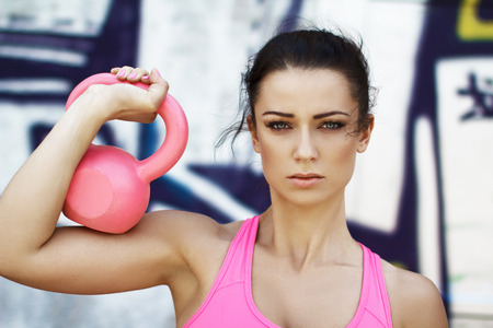 29891766 - woman holding pink kettlebell over shoulder, outdoor sport