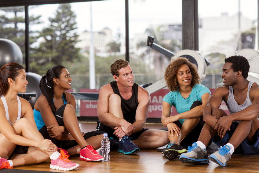 33875828 - multi-ethnic group relaxing before their gym glass