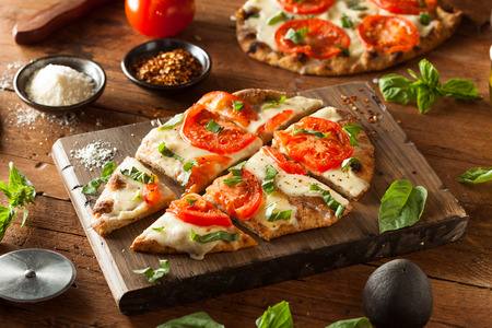38376193 - homemade margarita flatbread pizza with tomato and basil