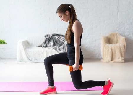 40037137 - athletic woman warming up doing weighted lunges with dumbbells workout exercise for butt legs at home healthy lifestyle sport bodybuilding concept.