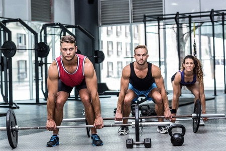 42329412 - portrait of a three muscular athletes lifting a barbell