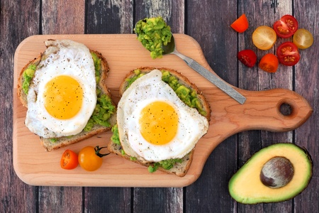 43849740 - avocado egg open sandwiches on whole grain bread with tomatoes on paddle board with rustic wood table