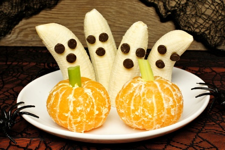 44662542 - healthy halloween treats, banana ghosts and orange pumpkins, on a plate with holiday decor