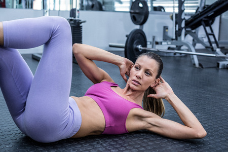 44816071 - muscular woman doing abdominal crunch at the crossfit gym