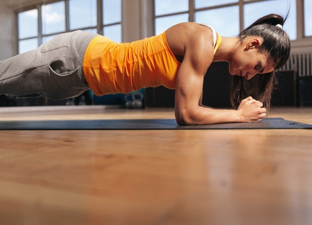 45175361 - young woman doing pilates, working on abdominal muscles. muscular female doing core workout in the gym.