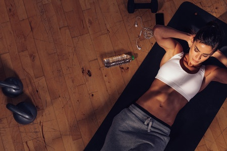 45175364 - overhead view of female doing abs workout at the gym. muscular young woman lying on exercise mat with her hands behind head doing stomach exercises.