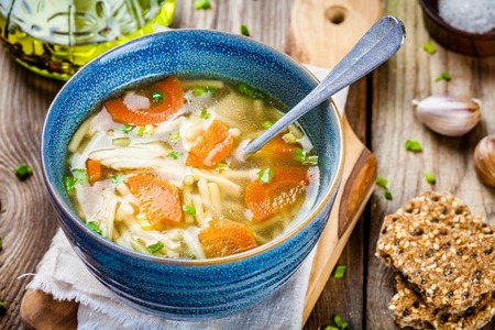50965886 - chicken noodle soup with carrots and green onions on wooden table