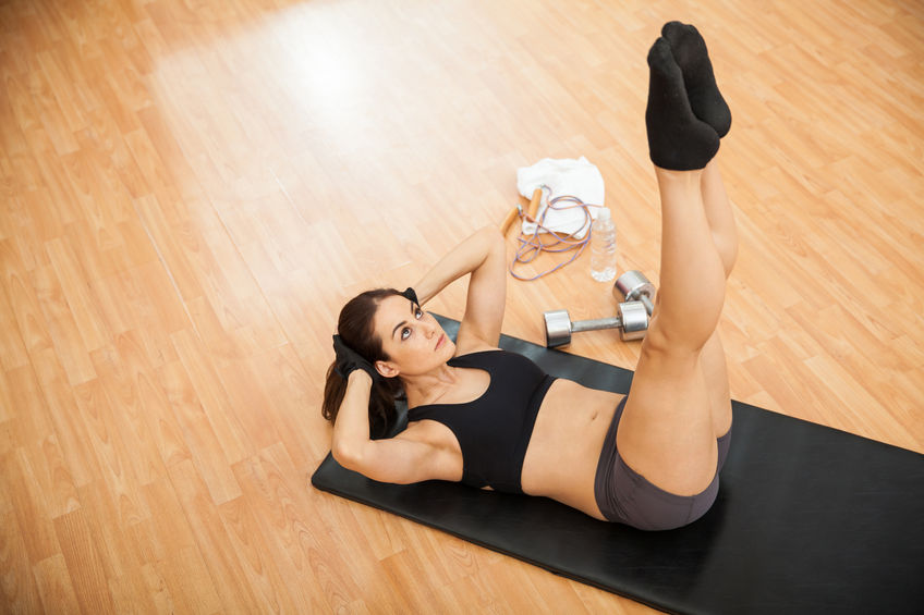 54131946 - top view of a young woman keeping her legs raised and doing crunches at the gym